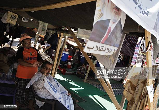 An Egyptian man gets his hair done at a makeshift barber shop nearby a sitin by members of Egypt's Muslim Brotherhood and supporters of ousted...