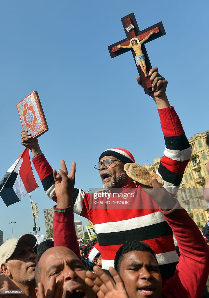 An Egyptian man, holding a cross and a Koran, takes part in a demonstration in Cairo's Tahrir square on February 8, 2013. Thousands took to the streets after opposition groups called for 'Friday of dignity' rallies demanding Egyptian President Mohamed Morsi fulfill the goals of the revolt that brought him to power.