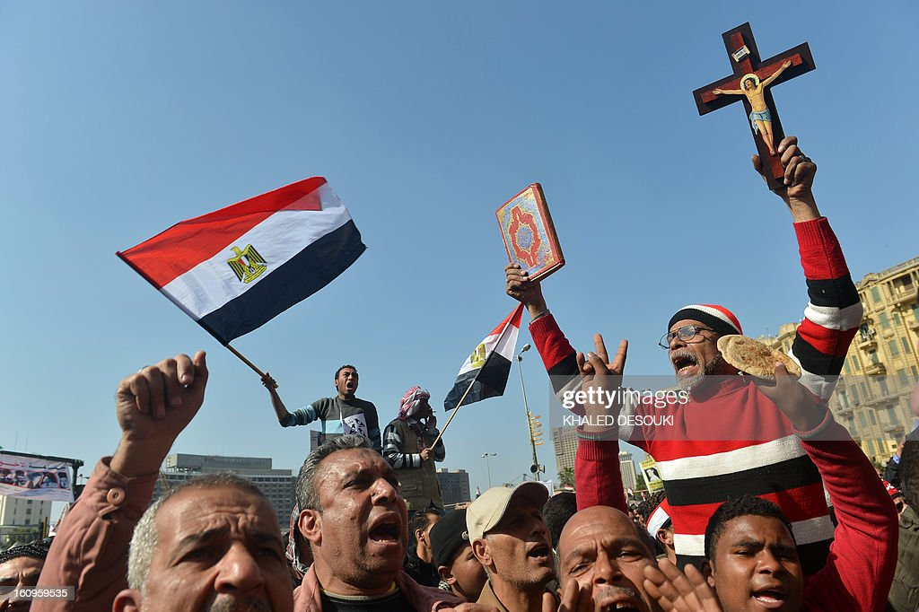 An Egyptian man, holding a cross and a Koran, takes part in a demonstration alongside others waving their national flag in Cairo's Tahrir square on February 8, 2013. Thousands took to the streets after opposition groups called for 'Friday of dignity' rallies demanding Egyptian President Mohamed Morsi fulfill the goals of the revolt that brought him to power.