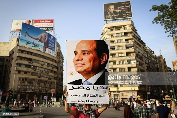 An Egyptian man holds up a portrait of exarmy chief Abdel Fattah alSisi as he celebrates in Cairo's Tahrir Square on June 3 2014 after Sisi won 969...