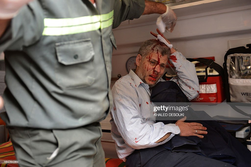 An Egyptian man is treated in an ambulance after being injured during clashes part of a protest of members of Egyptian Muslim brotherhood in front the party's headquarters in Cairo on March 22, 2013. A group of men stormed a Muslim Brotherhood office in the Egyptian capital, ransacking it and assaulting some of the group's members, the movement's spokesman told AFP.