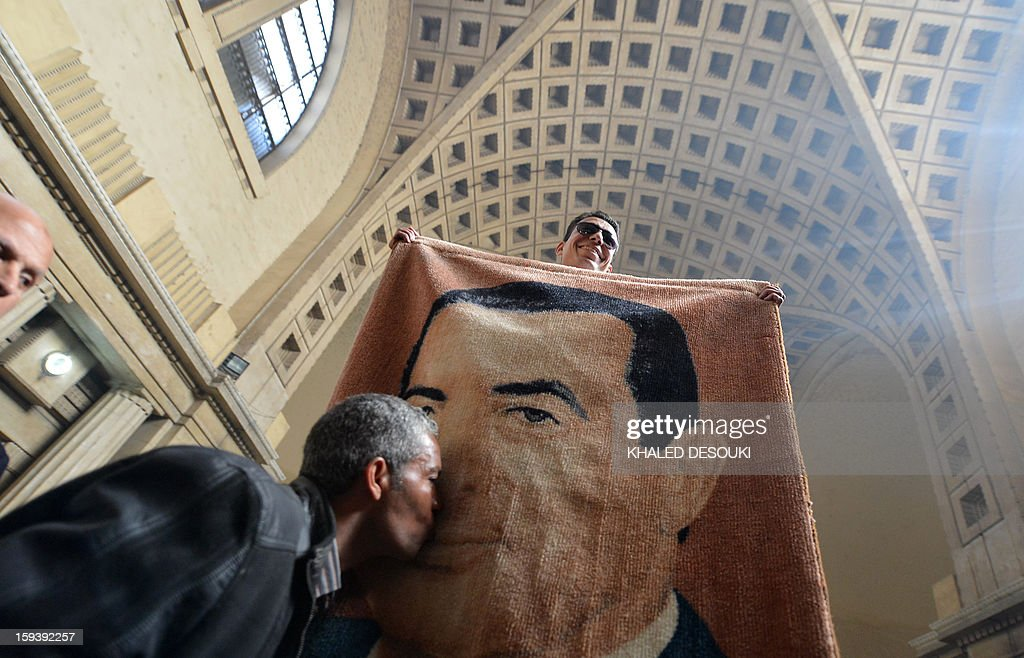 An Egyptian man kisses a tapestry with the portrait of former president Hosni Mubarak during a gathering in Cairo on January 13, 2013, after the court of Cessation, the top appeals court, accepted an appeal for a retrial of the ousted president. An Egyptian court ordered a retrial for former president Hosni Mubarak after accepting an appeal against the life sentence handed him for his involvement in the deaths of protesters in 2011. AFP PHOTO / KHALED DESOUKI