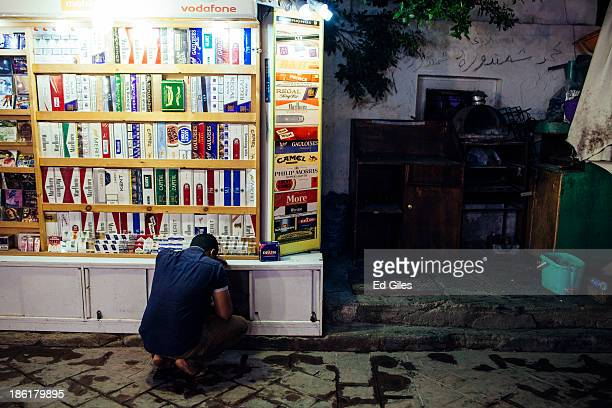 An Egyptian man kneels down at a small cigarette stall on a restaurant strip popular with tourists on October 26 2013 in the Red Sea resort town of...