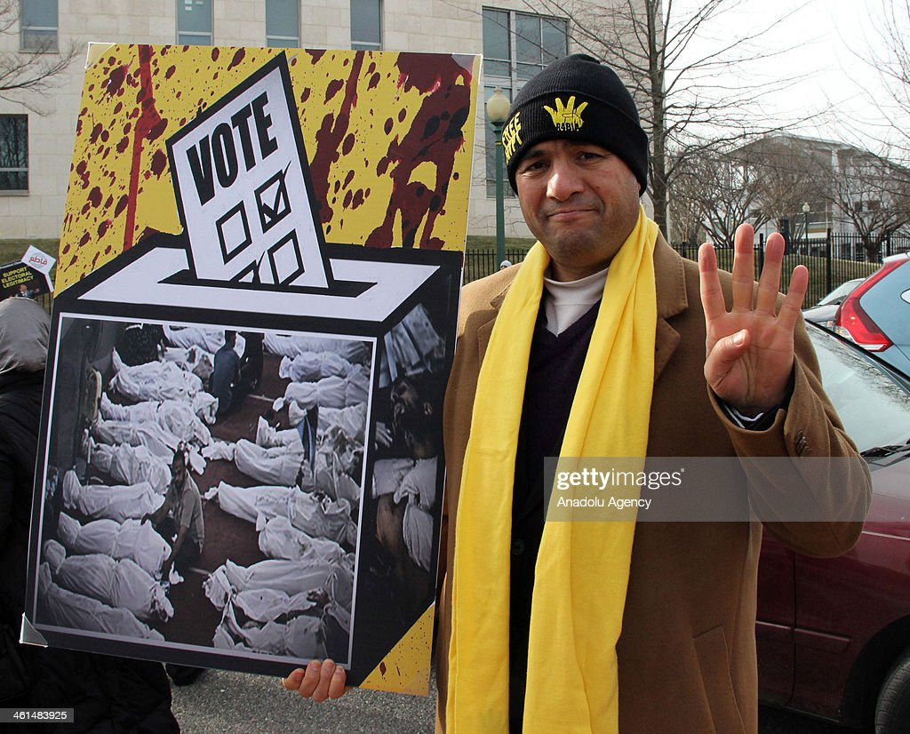 An Egyptian man living in US shows a rabia sign during the protest in front of the Egyptian Embassy in Washington against to be held a constitution referendum next week and the military coup in Egypt which is removed from the Egypt's first president Mohamed Morsi in Washington D.C., on January 9, 2014.