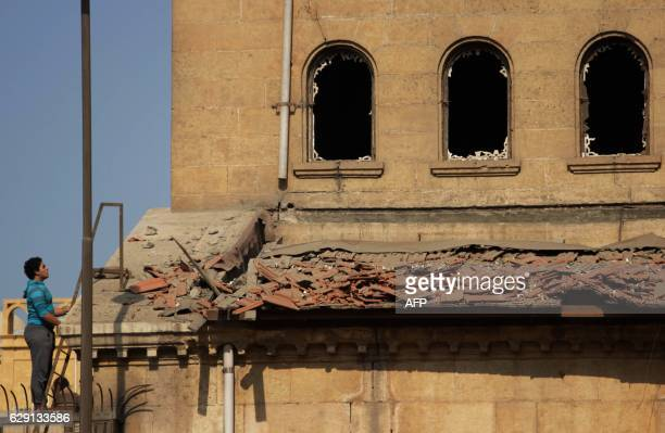 TOPSHOT An Egyptian man looks at the damage at the scene of a bomb explosion that targeted the Saint Peter and Saint Paul Coptic Orthodox Church on...