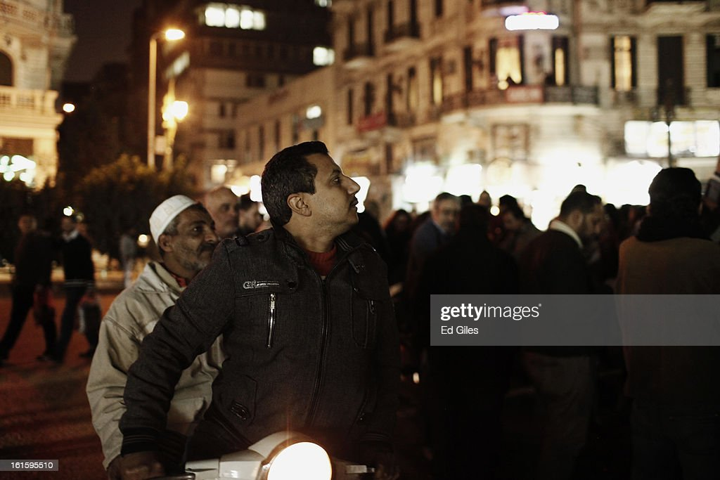 An Egyptian man on a motor scooter watches as other men and women take part in a march against sexual harassment at Talat Harb Square, on February 12, 2013 in central Cairo, Egypt. A few hundred Egyptian men and women gathered at the Egyptian capital's Talat Harb Square on Tuesday to demonstrate against the continuing problem of sexual harassment of Egyptian and foreign women during demonstrations across Egypt. (Photo by Ed Giles/Getty Images).