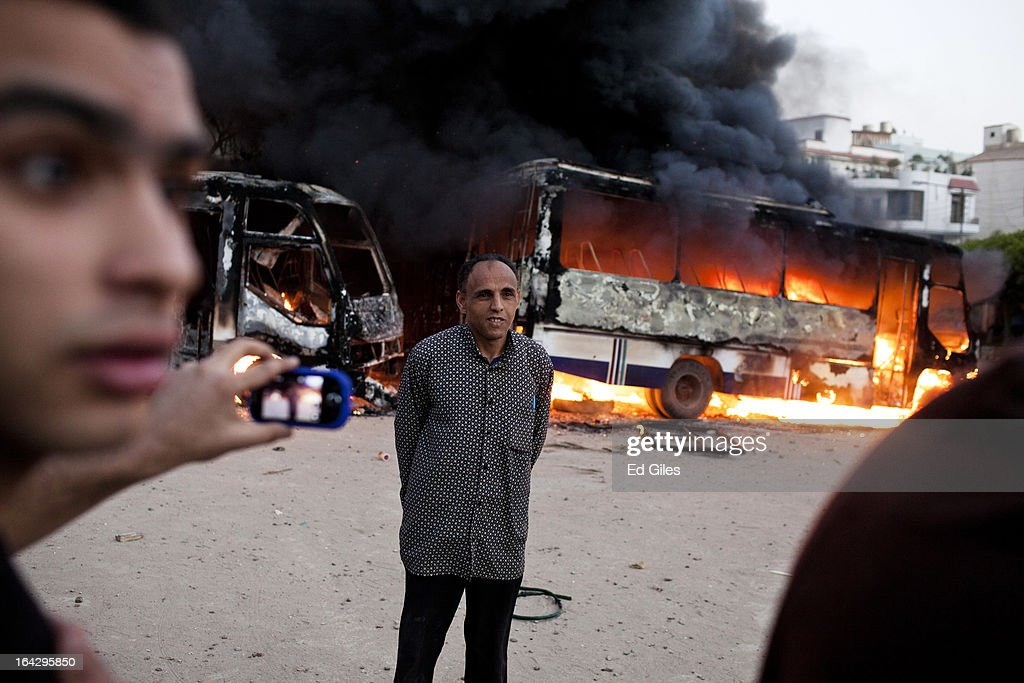 An Egyptian man poses before a burning bus reportedly belonging to the Muslim Brotherhood during clashes between opposition demonstrators and supporters of the Muslim Brotherhood on March 22, 2013 in Cairo, Egypt. Opposition demonstrators converged on the headquarters of the Muslim Brotherhood in the Cairo suburb of Muqattam to protest against the government of President Mohammed Morsi, who is closely connected to the Muslim Brotherhood movement.