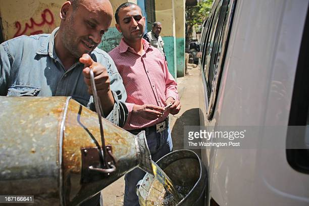 An Egyptian man pours blackmarket diesel into a fuel tank of a minibus in Cairo Egypt Thursday April 11 2013 Egypt's rapidly expanding black market...