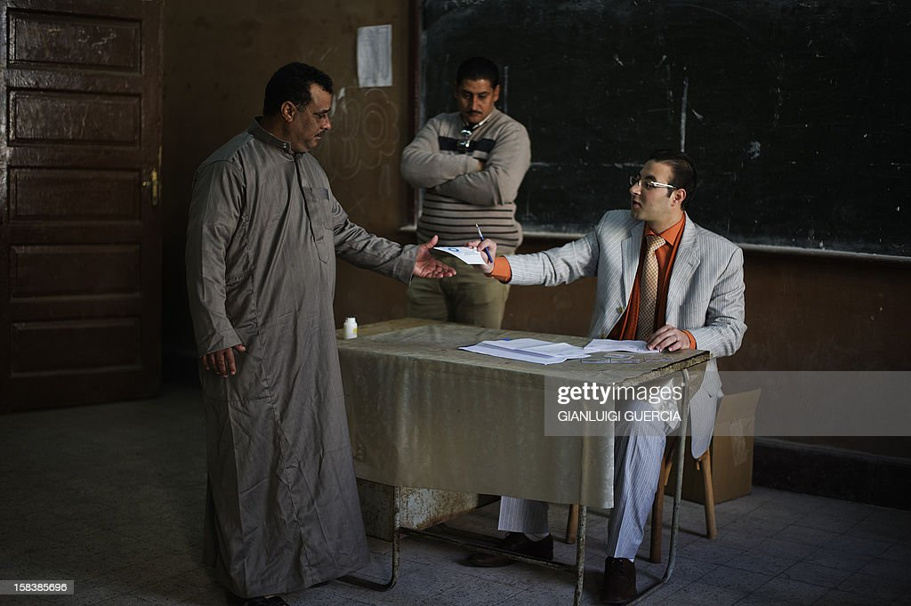 An Egyptian man (L) proceeds to cast his vote at a polling station in President Mohamed Morsi's hometown Zagazig in the Nile Delta on a new constitution supported by the ruling Islamists but bitterly contested by a secular-leaning opposition on December 15, 2012. Morsi's determined backing of the charter triggered the power struggle with the opposition, which is supported by judges who accuse the Islamists of overreaching.