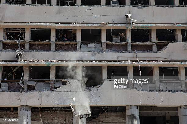 An Egyptian man pushes an air conditioner from the damaged Cairo Security Directorate building after a bomb attack in the Abdeen district on January...