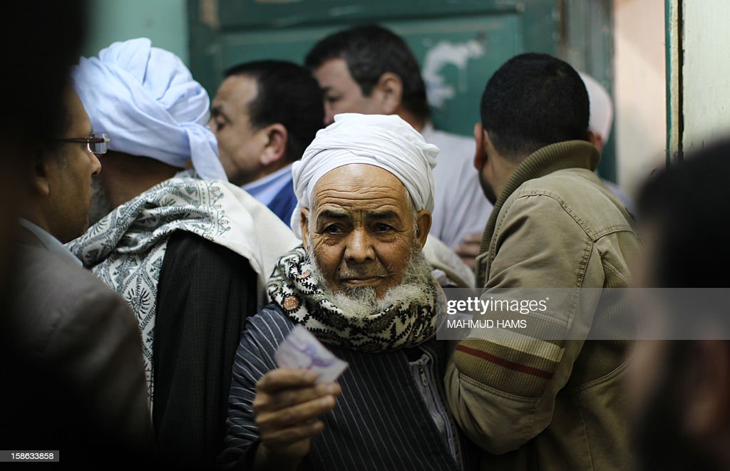 An Egyptian man readies to cast his ballot during the second round of a referendum on a new draft constitution in Giza, south of Cairo, on December 22, 2012. Egyptians are voting in the final round of a referendum on a new constitution championed by President Mohamed Morsi and his Islamist allies against fierce protests from the secular-leaning opposition.