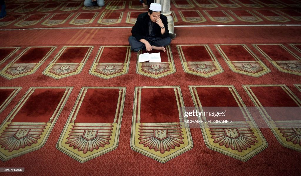 An Egyptian man reads from the Koran Islam's holy book inside AlAzhar mosque in the old city of Cairo on December 20 2014 AlAzhar mosque which was...