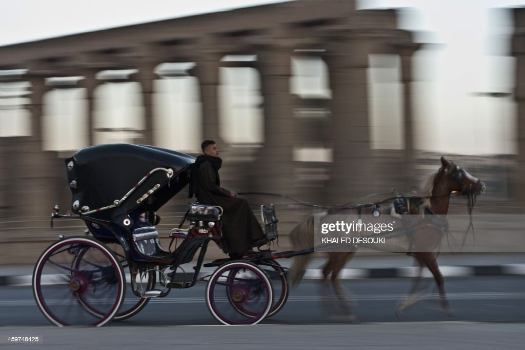 An Egyptian man rides his horse cart past the Temple of Luxor, in the southern Egyptian city of Luxor, on December 21, 2013. The 2011 revolution that toppled dictator Hosni Mubarak dealt a severe blow to the country's tourist industry, once a mainstay of Egypt's economy.