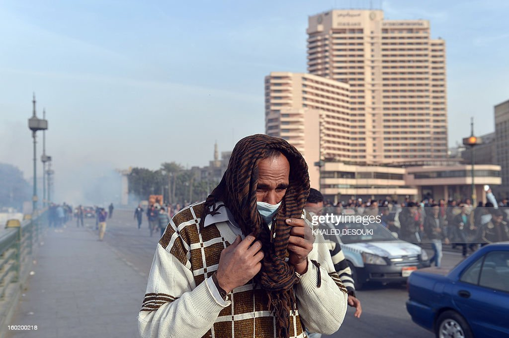 An Egyptian man runs for cover after a tear gas canister fired by riot policemen during clashes near Cairo's Tahrir Square on January 27, 2013. Clashes killed at least 31 people in Egypt's Port Said as violence raged into the early hours in several cities including the capital following death sentences passed on 21 football fans after a riot.