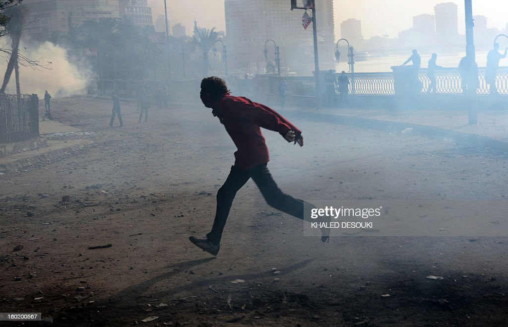 An Egyptian man runs for cover after a tear gas canister was fired by riot police during clashes near Cairo's Tahrir Square on January 27, 2013. Clashes killed at least 31 people in Egypt's Port Said as violence raged into the early hours in several cities including the capital following death sentences passed on 21 football fans after a riot. AFP PHOTO / KHALED DESOUKI