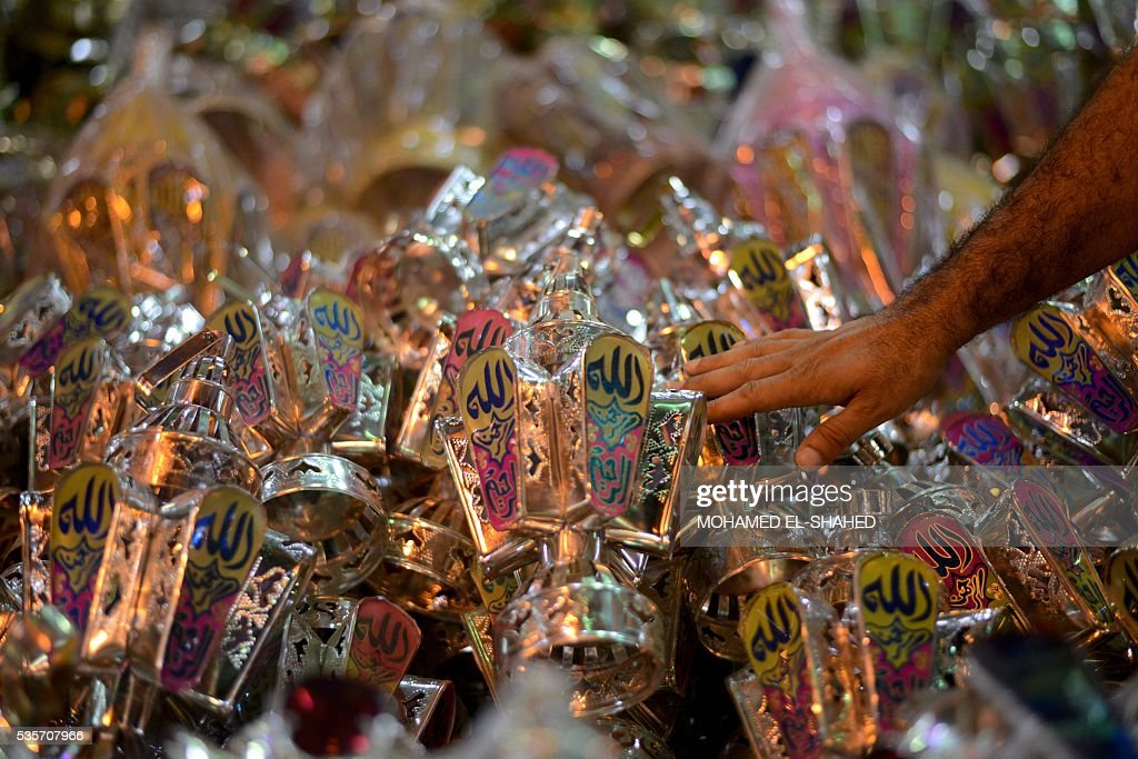 An Egyptian man selects a traditional lantern known in Arabic as 'Fanous', sold during the Muslim holy month of Ramadan in the Saida Zeinab district, in the capital Cairo, as the faithful prepare for the start of the holy month, on May 29, 2016. More than 1.5 billion Muslims around the world will mark the holy month which begins this week. Ramadan is the ninth month of the Muslim lunar calendar during which observant Muslims fast from dusk to dawn. / AFP / MOHAMED