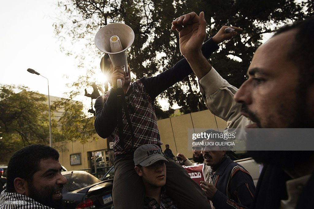 An Egyptian man shouts political and religious slogans on a megaphone as Muslim Brotherhood members demonstrate in support of Egypt's president Mohammed Morsi's new expanded powers and the drafting of a contested charter, highlighting Egypt's widening polarisation, outside Cairo's University on December 1, 2012 in Cairo.