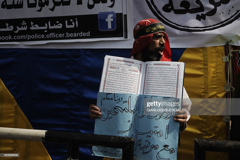 An Egyptian man shouts religious and political slogans while holding a copy of the Koran, Islam's holy book, and a sign reading 'God be with you, bearded officers' as hundreds of Salafists demonstrate over a lack of enforcement of a recent court order permitting bearded police officers to serve in Cairo on March 1, 2013.