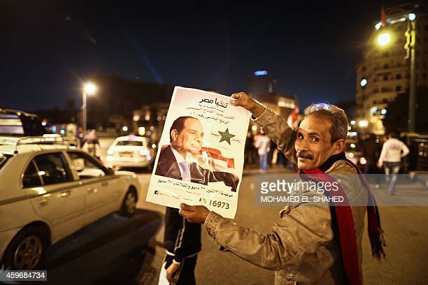 An Egyptian man shows a portrait of President Abdel Fattah alSisi on Tahrir Square in the capital Cairo on November 28 during a demonstration to show...