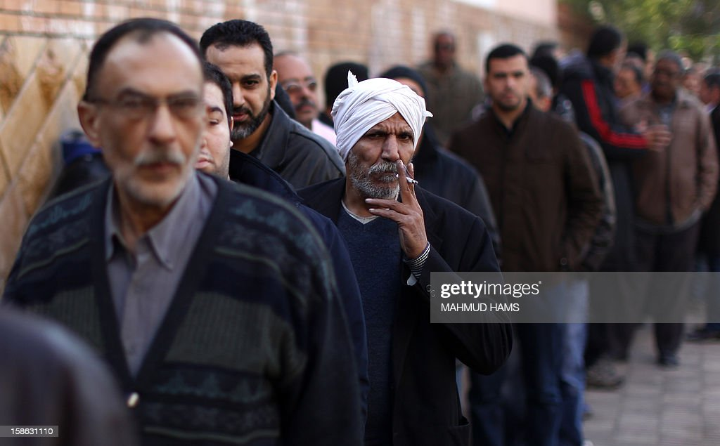 An Egyptian man smokes a cigarette as he queues with other voters outside a polling station during the second round of a referendum on a new draft constitution in Giza, south of Cairo, on December 22, 2012. Egyptians are voting in the final round of a referendum on a new constitution championed by President Mohamed Morsi and his Islamist allies against fierce protests from the secular-leaning opposition.