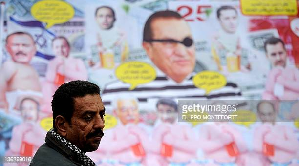 An Egyptian man stands in front of a cartoon banner depicting ousted president Hosni Mubarak and other regional leaders during a demonstration in...