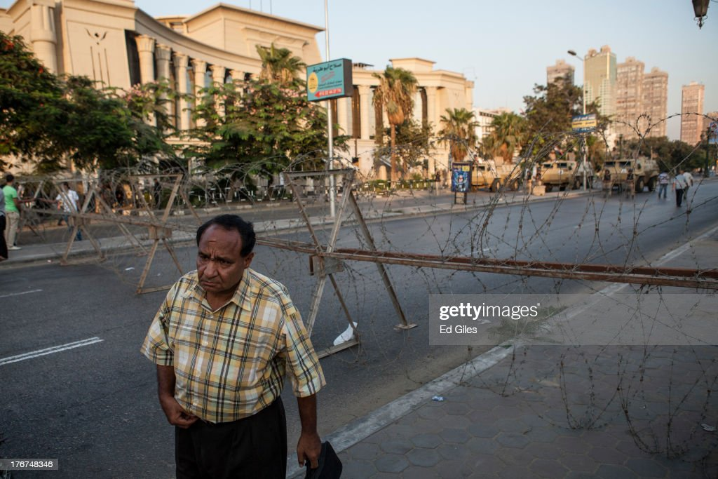 An Egyptian man stands in front of a military checkpoint at the Supreme Constitutional Court building on the Nile River corniche in the Maadi...