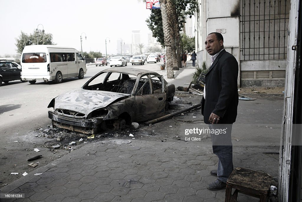 An Egyptian man stands on the street by the wreckage of a car damaged in violent clashes the previous night near Tahrir Square on January 27, 2013 in Cairo, Egypt. Violent protests continued across Egypt two days after the second anniversary of the Egyptian Revolution that overthrew former President Hosni Mubarak on January 25, and one day after the announcement of the death penalty for 21 suspects in connection with a football stadium massacre one year before. The verdict was announced in a case over the deaths of more than seventy fans of Egypt's Al-Ahly football club in a stadium massacre on February 1, 2012, in the northern city of Port Said, during a brawl that began minutes after the final whistle of a match between Al-Ahly and opposing side, Al-Masry. 21 fans of the opposing side, Al-Masry, were given the death penalty, a verdict that must now be approved by Egypt's Grand Mufti. (Photo by Ed Giles/Getty Images).