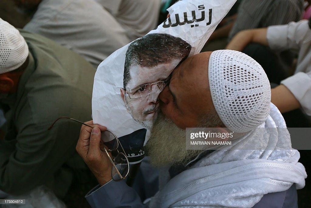 An Egyptian man, supporter of the Muslim Brotherhood and Egypt's ousted president Mohamed Morsi kisses a poster of him as worshipers gather for a dusk payer outside Cairo's Rabaa al-Adawiya mosque on July 11, 2013, during the second day of Islam's holy fasting month of Ramadan. The people of Egypt are marking the Muslim fasting month of Ramadan amid soaring tensions following last week's ouster by the military of Islamist president Mohamed Morsi.