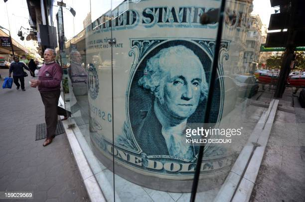 An Egyptian man walks out of an exchange store in the capital Cairo on January 6 2013 A top International Monetary Fund official will visit Egypt on...