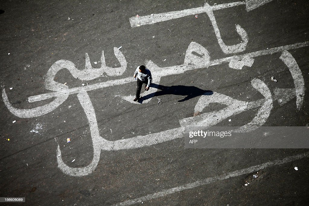 An Egyptian man walks over a graffiti reading 'Morsi Go' on November 25, 2012 at Egypt's landmark Tahrir square in Cairo. Scuffles broke out between journalist supporters and foes of the Muslim Brotherhood at an emergency union meeting over Islamist President Mohamed Morsi's decree giving him broad powers, a journalist who was there reported.