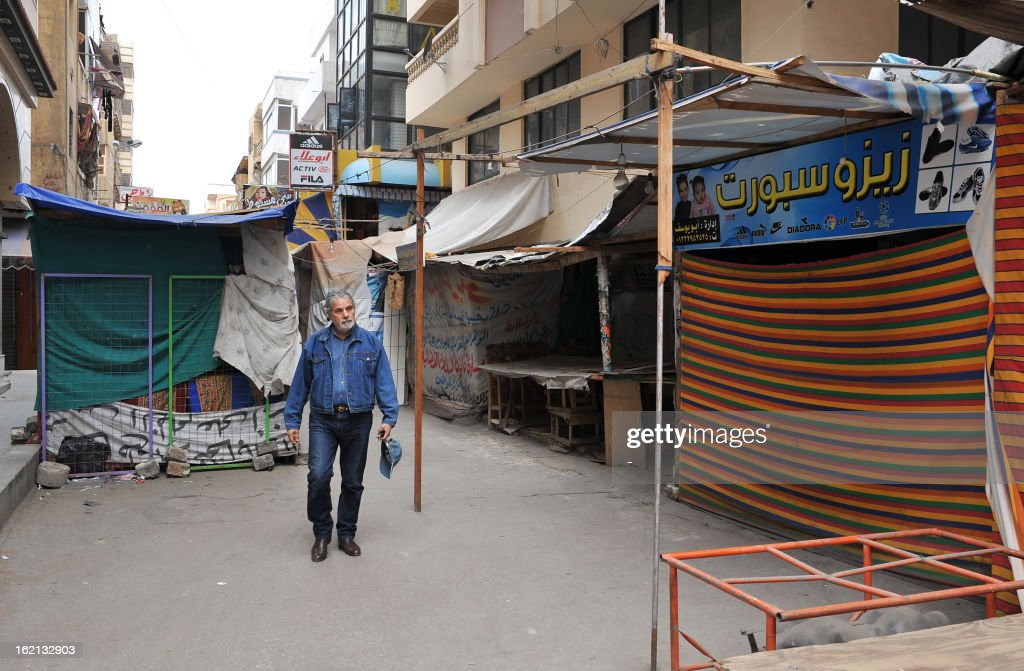 An Egyptian man walks passed closed shops in Port Said on February 19, 2013. Credit-ratings agency Moody's said earlier this month that it has downgraded Egypt's government bond ratings by one notch from B2 to B3, citing the intensification of civil unrest and sliding foreign exchange reserves. AFP PHOTO / STR