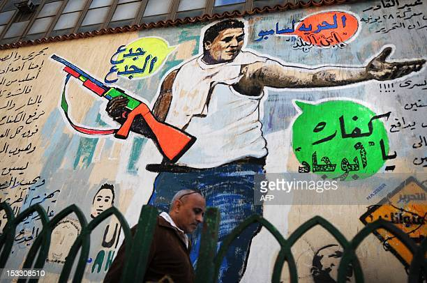 An Egyptian man walks past a graffiti depicting Mohamed Gad a protester who became famously known as 'Sambo' in central Cairo on March 17 2012 Sambo...