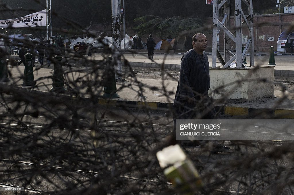 An Egyptian man walks past barbed wire outside the presidential palace in Cairo on December 13, 2012. Egypt's crisis showed no sign of easing as the army delayed unity talks meant to ease political divisions and the opposition set near-impossible demands for taking part in a looming constitutional referendum. AFP PHOTO/GIANLUIGI GUERCIA