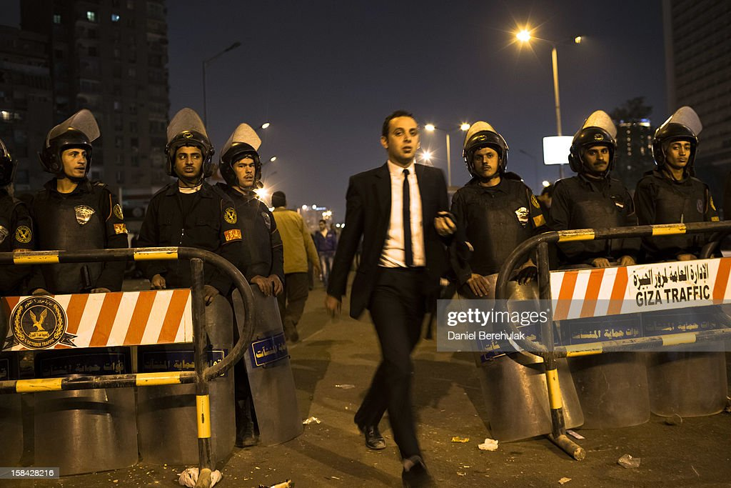 An Egyptian man walks past riot police as they stand guard in front of Dokki police station on December 16, 2012 in Cairo, Egypt. Egyptian police were on high alert after news of a planned protest by Salafist supporters of Hazem Abu Ismail, after an attack on WAFD party headquarters last night on election day. The protest was cancelled after an announcement on Hazem Abu Ismail's Facebook account.