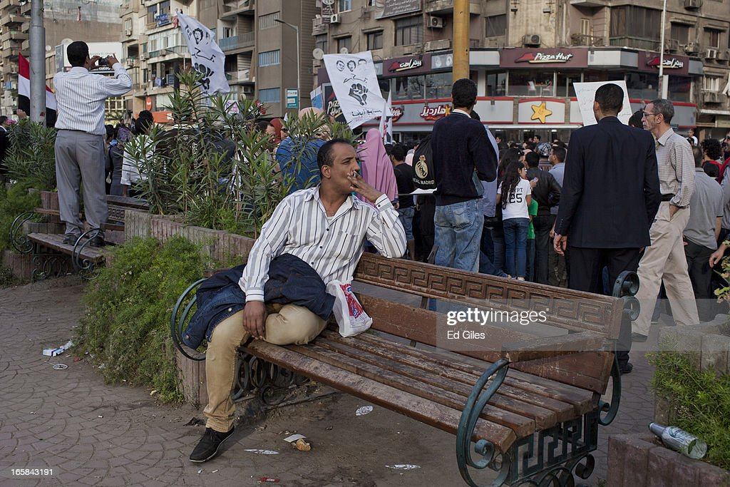 An Egyptian man watches a group of protesters march through the Cairo suburb of Mohandessen during a demonstration against Egyptian President Mohammed Morsi and the government of the Muslim Brotherhood on April 6, 2013 in Cairo, Egypt. Hundreds of protesters gathered at multiple locations across Cairo and other cities in Egypt to mark the fifth anniversary of the April 6 movement, a major revolutionary group made up of youth and workers in Egypt.