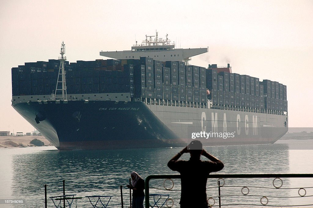 An Egyptian man watches the largest and the newest container ship in the world, the British flagged CMA CGM Marco Polo, sails through the Suez Canal on December 2, 2012, as it passes the port of Ismailia, 120 km northeast of the Egyptian capital Cairo. The South Korean built Marco Polo can carry some 16 000 containers or 167 000 tons.