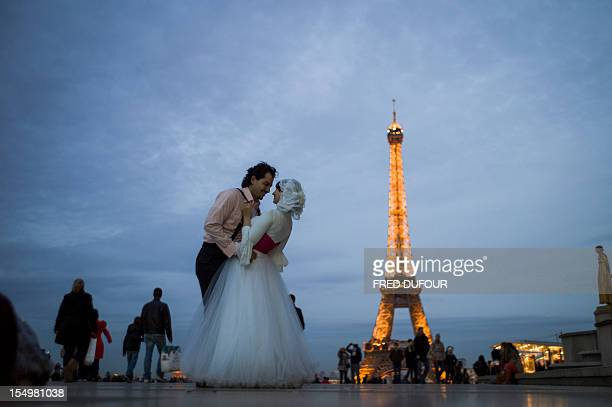 An Egyptian married couple kiss on the Trocadero esplanade in front of the Eiffel tower on October 29 in Paris AFP PHOTO / FRED DUFOUR