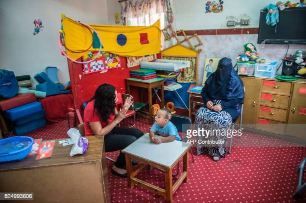 An Egyptian mother of a boy with disability watches his activities at the SETI center a section of Catholic charity Caritas in the capital Cairo on...