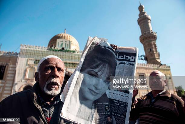 An Egyptian mourner holds a newspaper showing a full page obituary showing the face of the late popular singer and actress Shadia during her funeral...