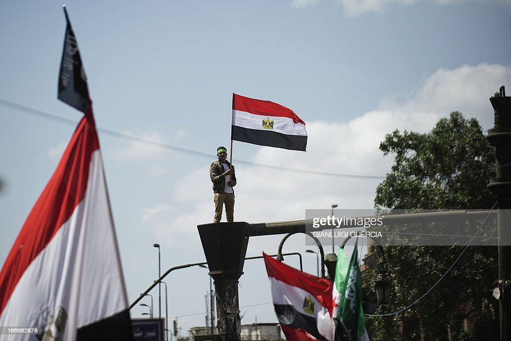 An Egyptian Muslim Brotherhood supporter waves his national flag on top of a lamp post during a protest in front of the High Court in Cairo demanding a purge in the Egyptian judicial system on April 19, 2013.