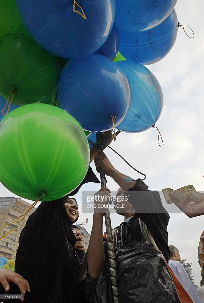 An Egyptian Muslim women reaches up to select a balloon from a vendor during a street celebration in Cairo, early 13 October 2007, after a special daybreak prayer for the first day of Eid al-Fitr, marking the end of the fasting month of Ramadan. Piety, defiance and bloodshed marked the feast of Eid al-Fitr, ending the holy month of Ramadan, across much of the Middle East. Eid al-Fitr is a three-day festival. On the first day, Muslims gather early in the morning in outdoor locations or mosques to perform the Eid prayer. This consists of a sermon followed by a short congregational prayer.