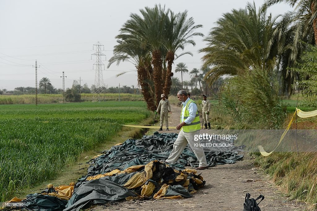 An Egyptian official with the Civil Aviation Authority (C) inspects the site of a hot air balloon accident in Luxor on February 26, 2013. A hot air balloon exploded and plunged to earth at Egypt's ancient temple city of Luxor during a sunrise flight, killing up to 19 tourists, including Asians and Europeans, sources said.