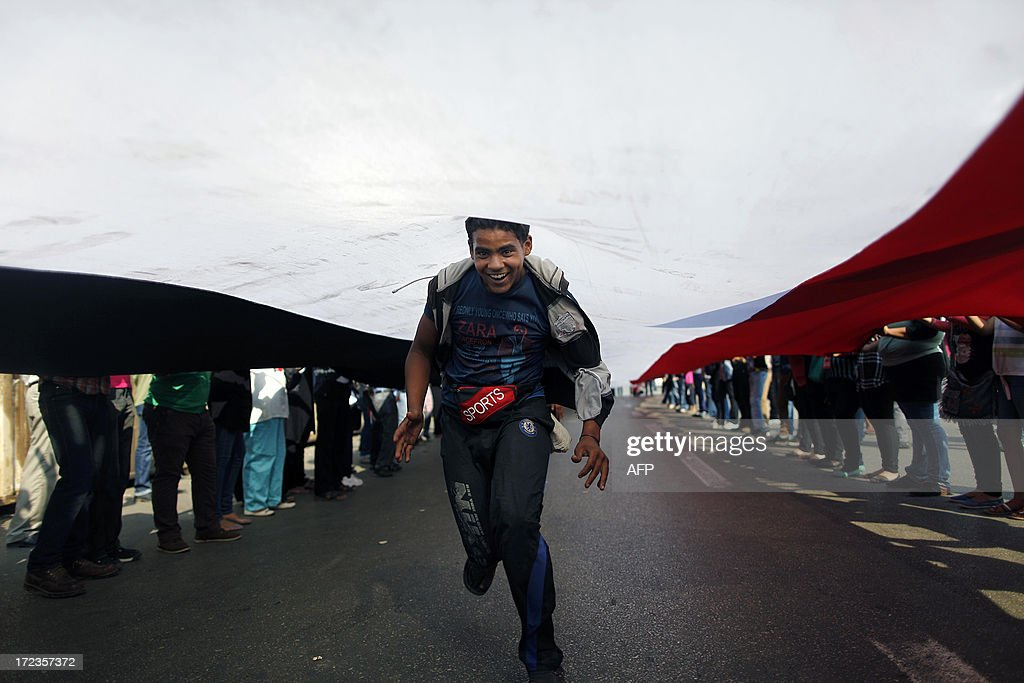 An Egyptian opposition demonstrator, runs down the length of a long national flag being held by protesters calling for the ouster of President Mohamed Morsi, outside the presidential palace in Cairo, on July 2, 2013. Egypt's political crisis deepened as Islamist President Morsi snubbed an army ultimatum threatening to intervene if he did not meet the demands of the people, and five ministers led a spate of government resignations. AFP PHOTO/MAHMUD KHALED