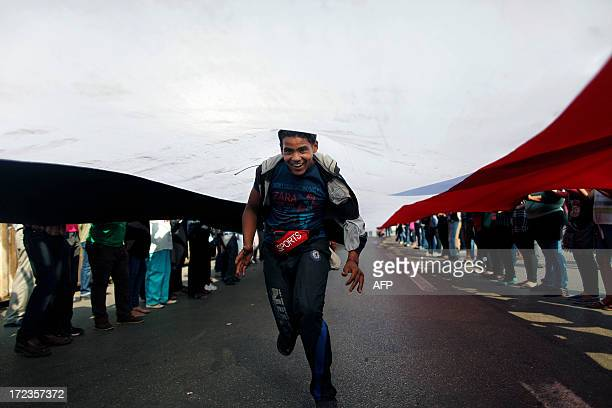 An Egyptian opposition demonstrator runs down the length of a long national flag being held by protesters calling for the ouster of President Mohamed...