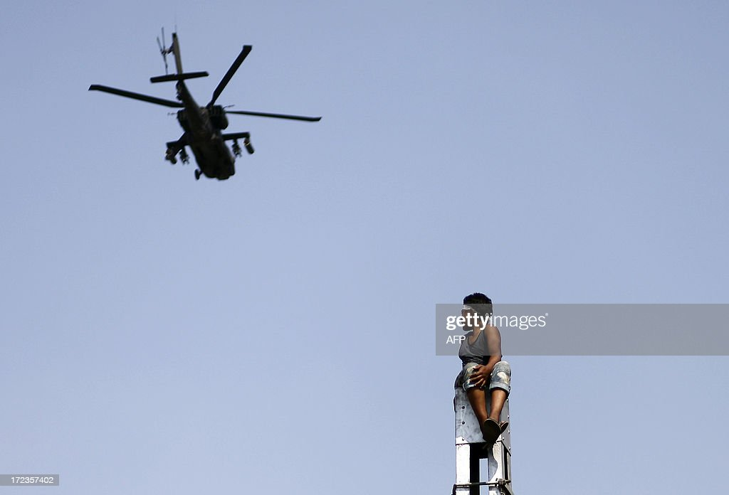 An Egyptian opposition demonstrator sits at the top of a column watching a military helicopter fly by, as protesters (unseen) call for the ouster of President Mohamed Morsi outside the presidential palace in Cairo, on July 2, 2013. Egypt's political crisis deepened as Islamist President Morsi snubbed an army ultimatum threatening to intervene if he did not meet the demands of the people, and five ministers led a spate of government resignations. AFP PHOTO/MAHMUD KHALED