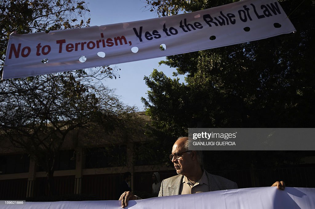 An Egyptian opposition protester holds a banner in front of the Supreme Constitutional Court (SCC) on the banks of the Nile in Cairo ahead of a court rule on the legality of an Islamist-dominated panel that drafted the country's constitution, on January 15, 2013. Egypt's top court was to rule whether Egypt's Islamist-dominated Senate should be dissolved as well as on the validity of a panel that wrote the country's controversial constitution.