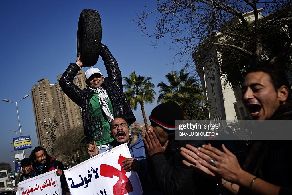 An Egyptian opposition protester holds a tire symbolizing President Mohamed Morsi's nickname 'spare tire' during a gathering in front of the Supreme Constitutional Court (SCC) on the banks of the Nile in Cairo in support of a court rule on the legality of an Islamist-dominated panel that drafted the country's constitution, on January 15, 2013. Egypt's top court was to rule whether Egypt's Islamist-dominated Senate should be dissolved as well as on the validity of a panel that wrote the country's controversial constitution. Morsi earned this nickname because he was Muslim Brotherhood's backup candidate behind Mahmoud Ezzat and Khairat el-Shater who was disqualified by election authority.