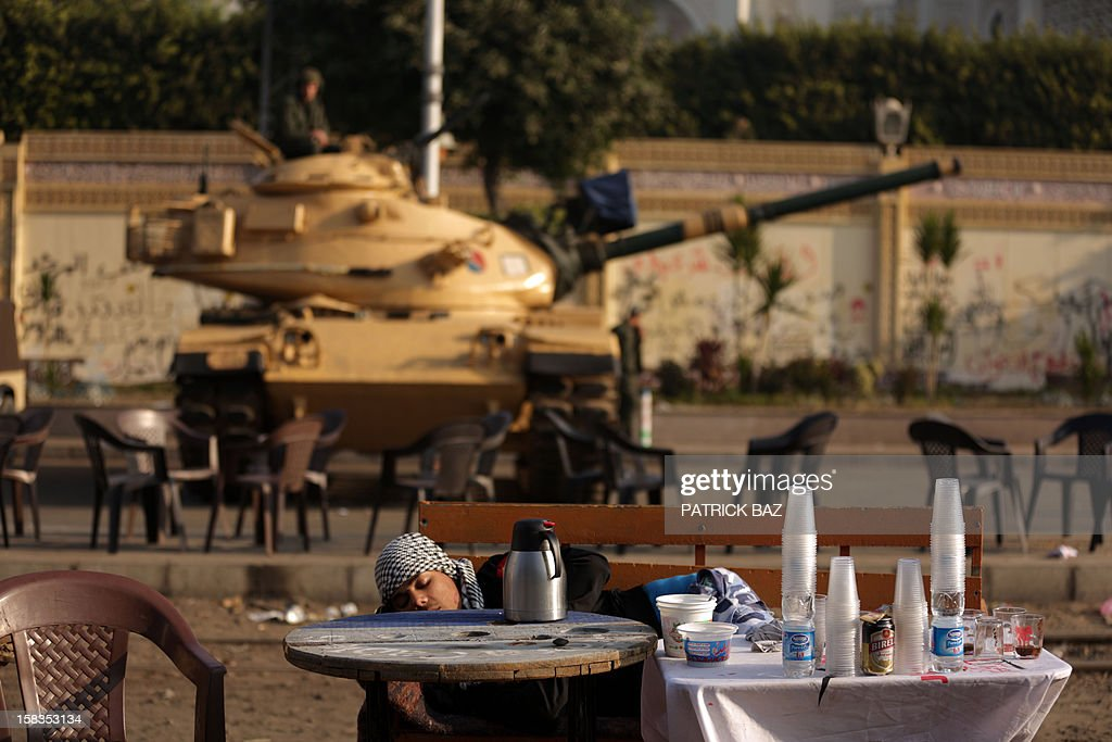 An Egyptian opposition protester sleeps in front of a Republican Guard tank stationed outside the presidential palace in Cairo on December 14, 2012. Weeks of protests and violent clashes between rival camps that left eight people dead last week have failed to dissuade Egypt's President Mohamed Morsi from holding the referendum, which will be staggered over a week.