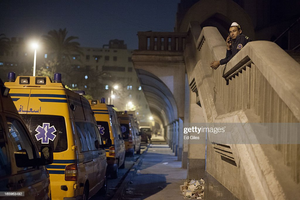 An Egyptian paramedic speaks on a mobile phone near a line of ambulances parked in the grounds of the St Mark's Cathedral in the Cairo suburb of Abasseyya during clashes with Egyptian riot police and groups of plain-clothed men on April 7, 2013 in Cairo, Egypt. Clashes began in and around the Cathedral grounds after a funeral procession for two coptic protesters killed during clashes on April 5 was attacked by unknown assailants on Sunday afternoon. (Photo by Ed Giles/Getty Images).