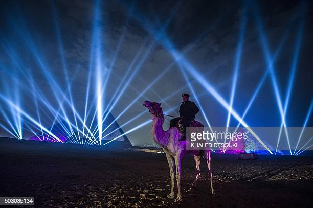 TOPSHOT An Egyptian policeman riding a camel stands guard during New Year celebrations in front of the pyramids near the Egyptian capital Cairo on...